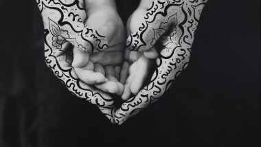 Shirin Neshat, Bonding, 1995. Photograph of a pair of children's hands resting on top of a pair of adult's hands (which have calligraphy drawn on them).