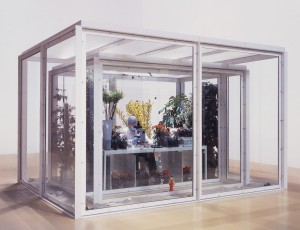 Damien Hirst - The Collector, 2003-2005, glass, painted steel, silicone rubber, aluminium, nylon netting, Formica, MDF, chair, animatronic man in laboratory wear, microscope, radiators, humidifiers, potted plants, flowers, live butterflies, butterfly specimens, cardboard and polystyrene specimen
