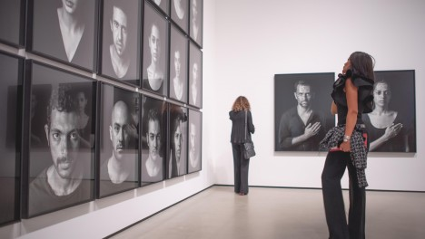 Photo of visitor looking at Shirin Neshat's works.