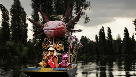 Three women sitting in an axolotl-shaped boat on a pond