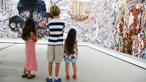 "A family looks at a Takashi Murakami's painting ""In the Land of the Dead, Stepping on the Tail of a Rainbow"""