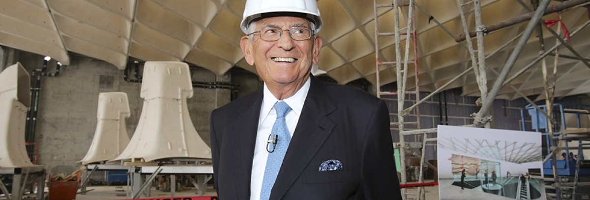 Eli Broad wearing a white hard hat and a dark suit standing at the construction site for The Broad Museum