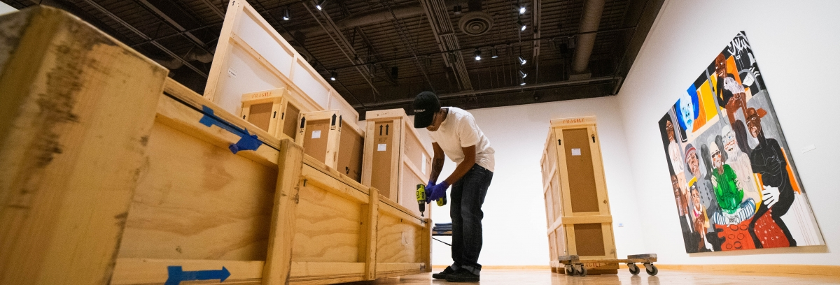 Preparator's Apprentice Nya Abudu packs a crate at the California African American Museum. (Photo by Kya Lou)