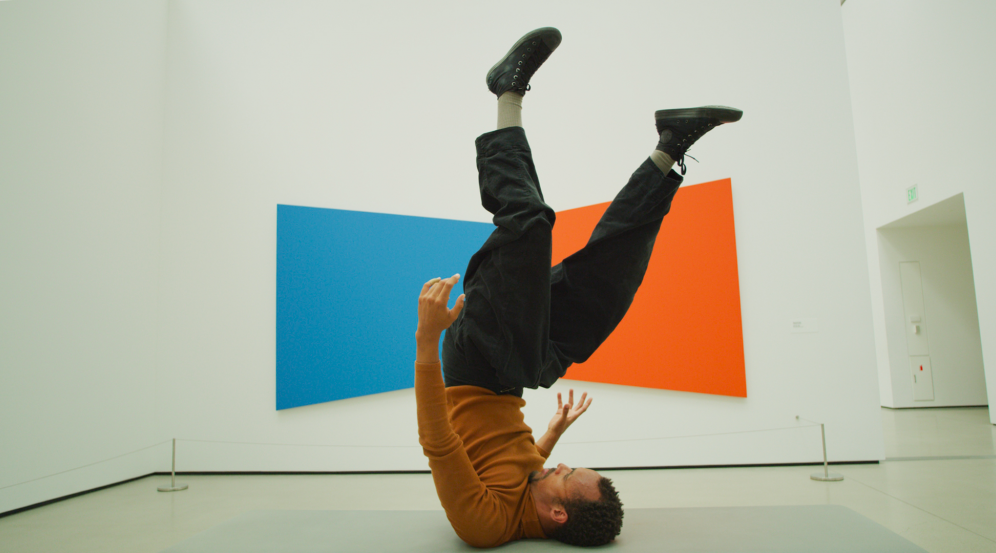 Image of Mike Tyus performing in front of a painting by Ellsworth Kelly in The Broad museum