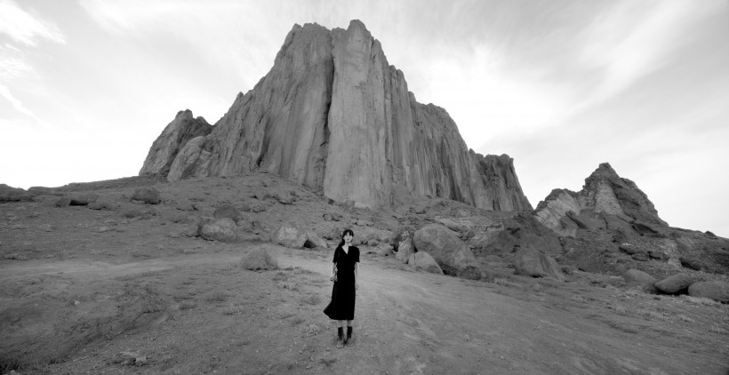 Video still of woman in front of a rocky landscape in New Mexico. Shirin Neshat, Land of Dreams video still, 2019.