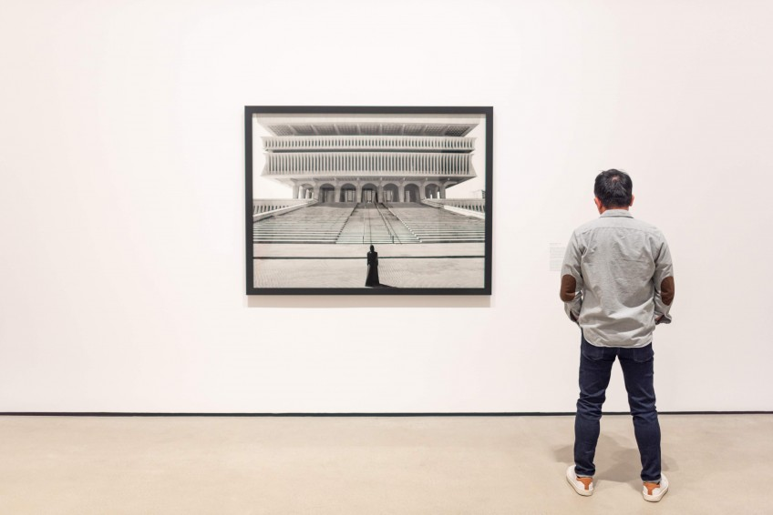 Photo of visitor looking at Shirin Neshat's work.