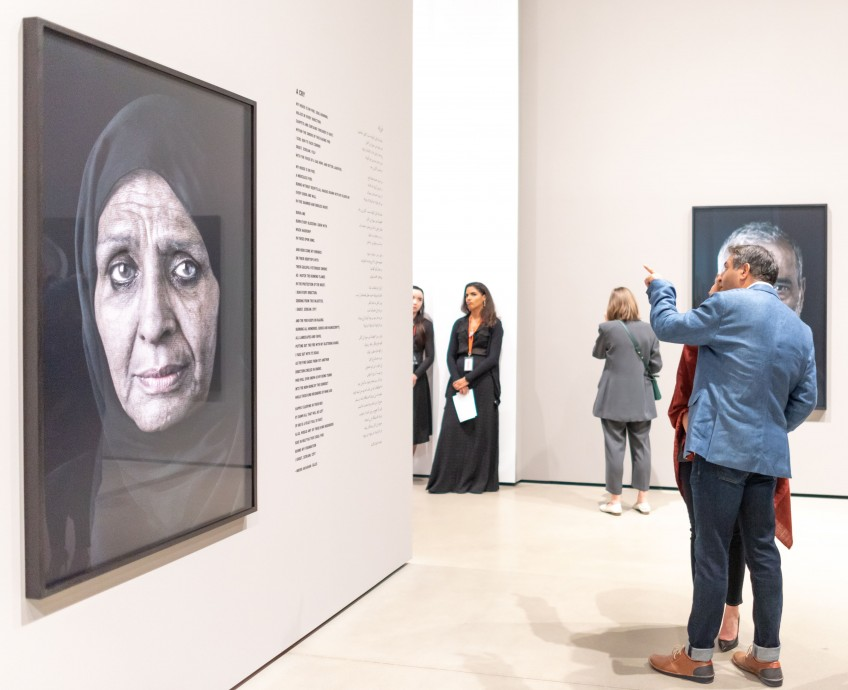 Photo of visitors looking at Shirin Neshat's work.